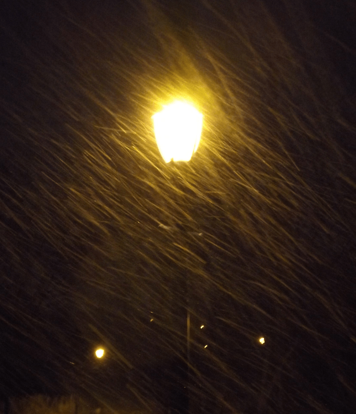 blowing-snow-night-yellow-lamppost