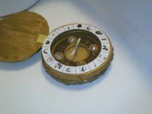Simple alethiometer used as birthday invitation, from side angle